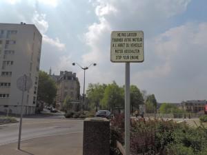 Mise en place d'un panneau trilingue en juin 2012, interdisant de laisser tourner les moteurs des véhicules à l'arrêt. Depuis 2007, ce panneau n'était qu'en français.